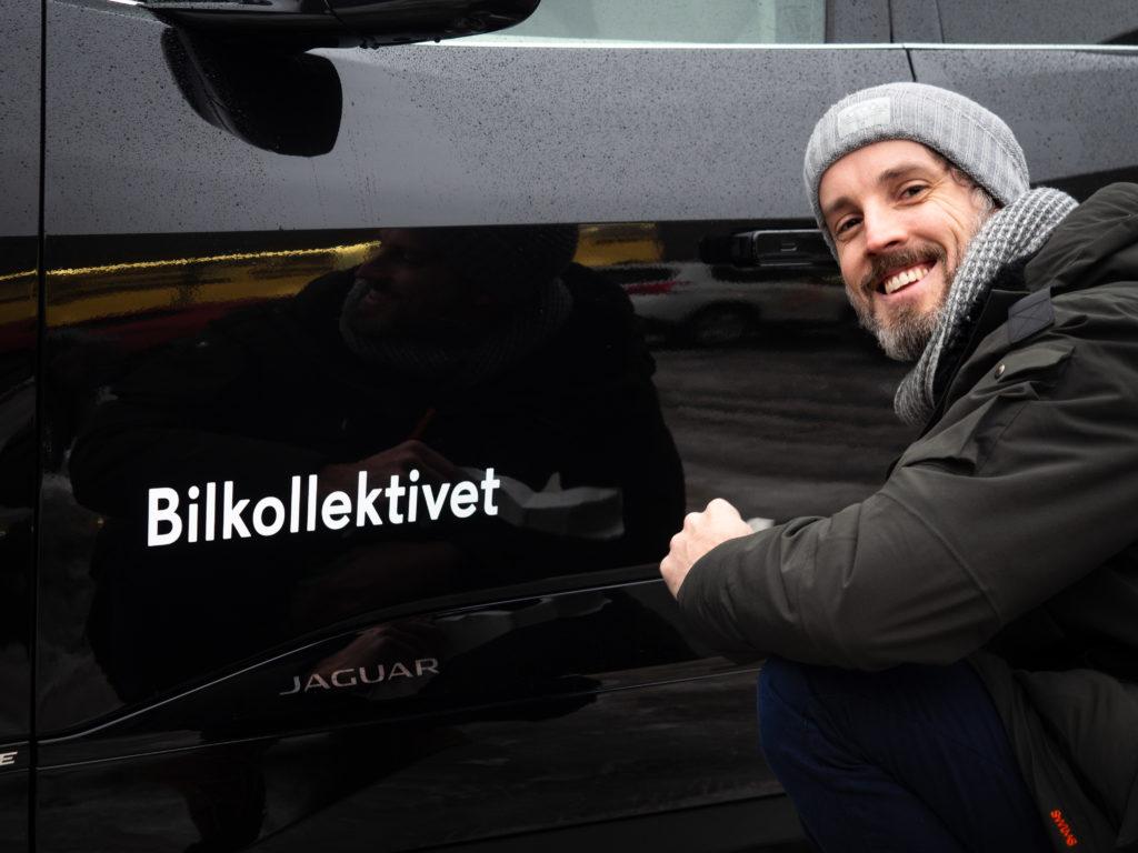 Haakon hals foran en sort bybil med teksten bilkollektivet på.
