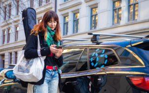 Jente som ser på telefonen sin. Hun har gitar på ryggen og går ved siden av en bybil.